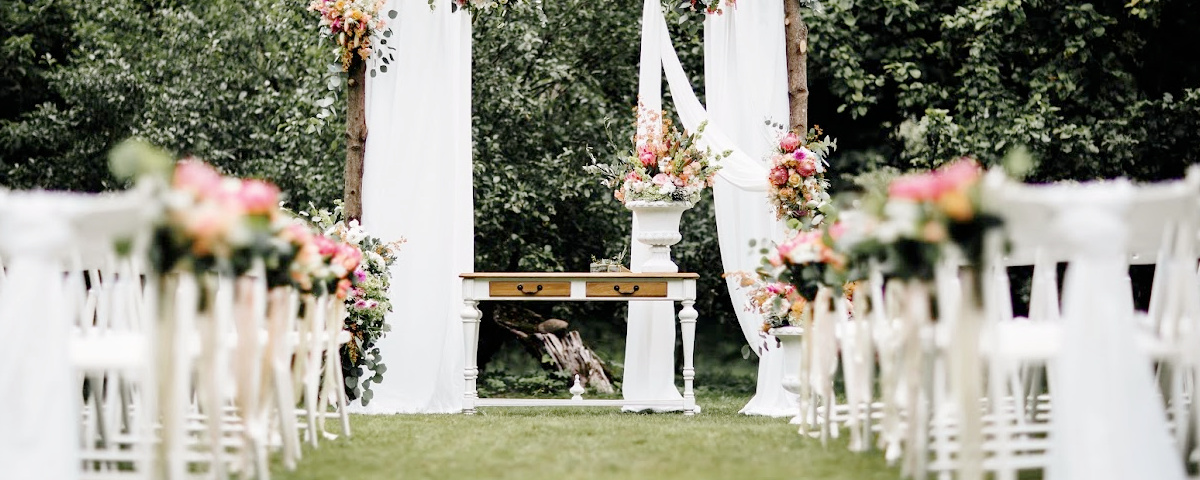 Decorated luxury wedding ceremony place in the garden. White empty chairs and arch decorated with flowers.