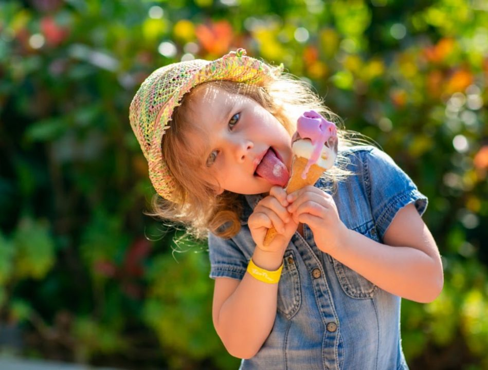Curly haired little girl in a sun hat licking ice cream cone